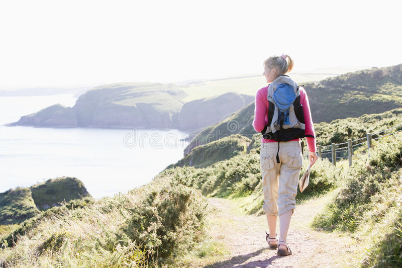 Frau, die auf cliffside Pfad geht lizenzfreies stockfoto