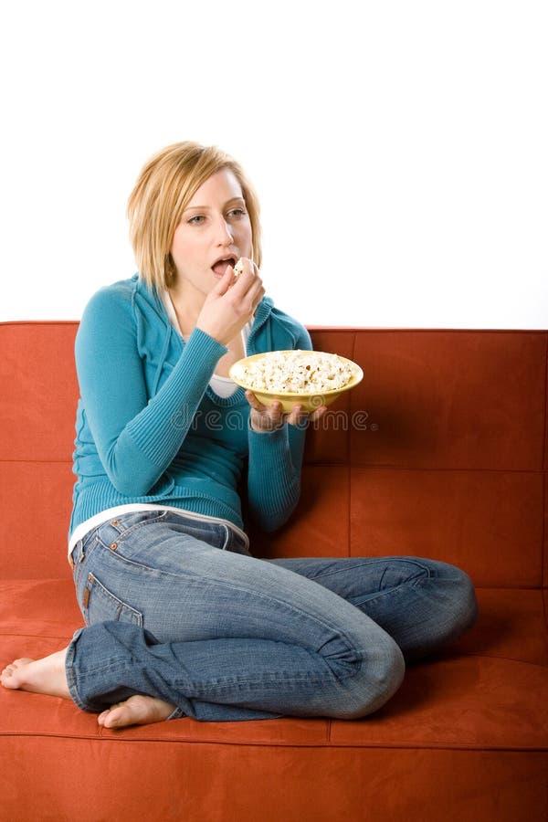 Frau, die auf Couch isst lizenzfreie stockfotos
