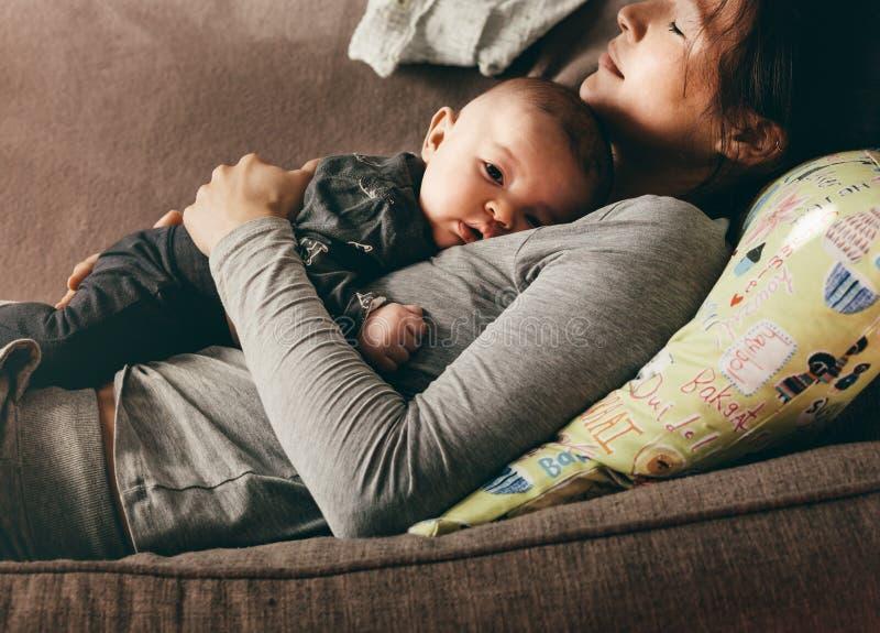 Frau, die auf Couch mit den Augen geschlossen liegt, ihr Baby halten lizenzfreie stockbilder