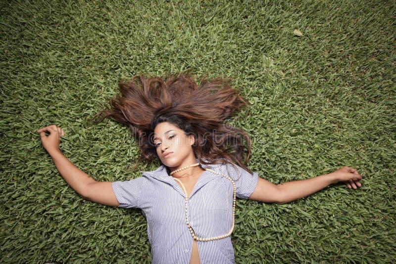 Frau, die auf das Gras legt lizenzfreie stockbilder