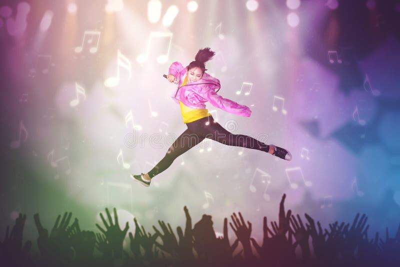 Frau, die auf das Konzertstadium singt und springt stockfotos