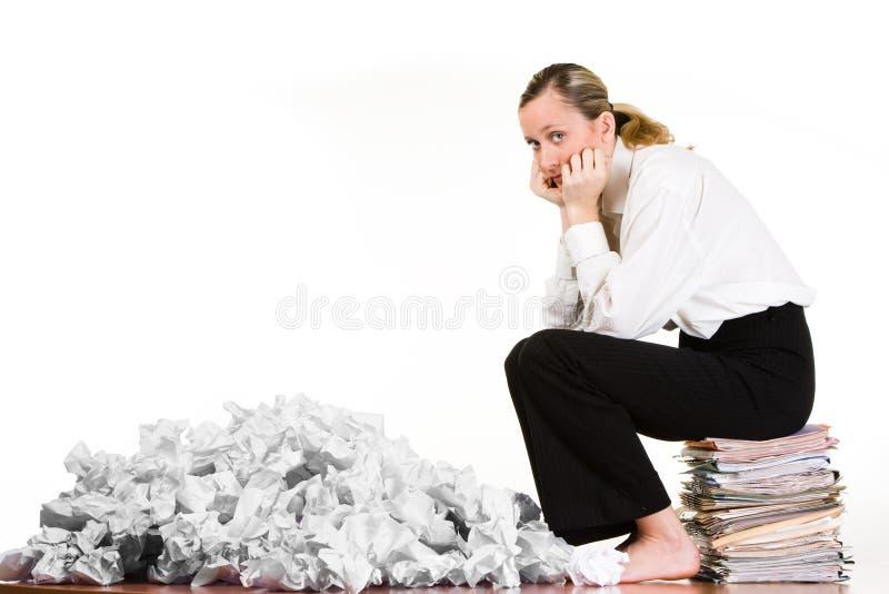 Frau, die auf Dateien sitzt lizenzfreie stockbilder