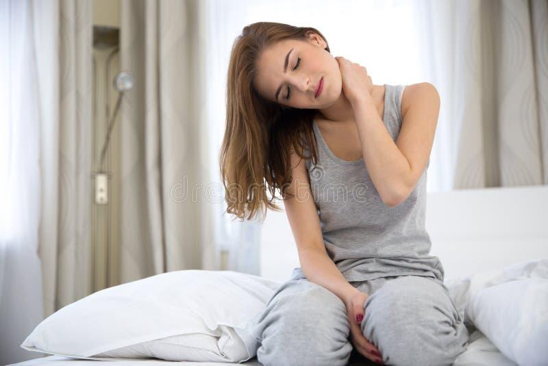 Frau, die auf dem Bett mit den Schmerz im Hals sitzt stockbild
