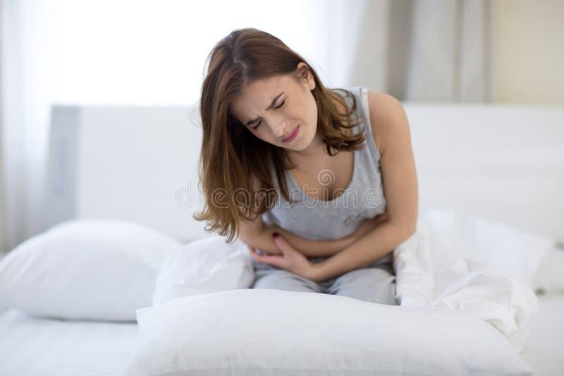 Frau, die auf dem Bett mit den Schmerz sitzt stockfotografie