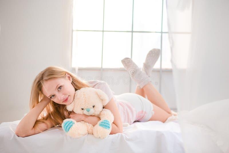 Frau, die auf dem Bett mit Teddybären liegt stockbilder