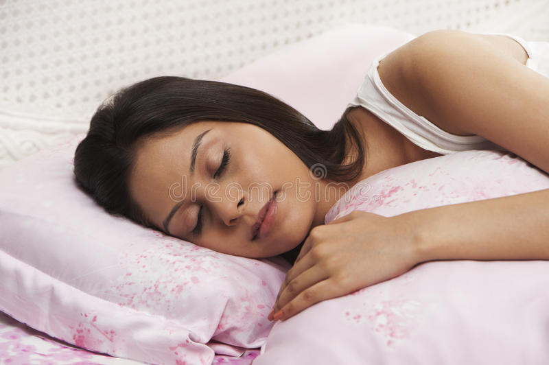 Frau, die auf dem Bett schläft stockfotografie
