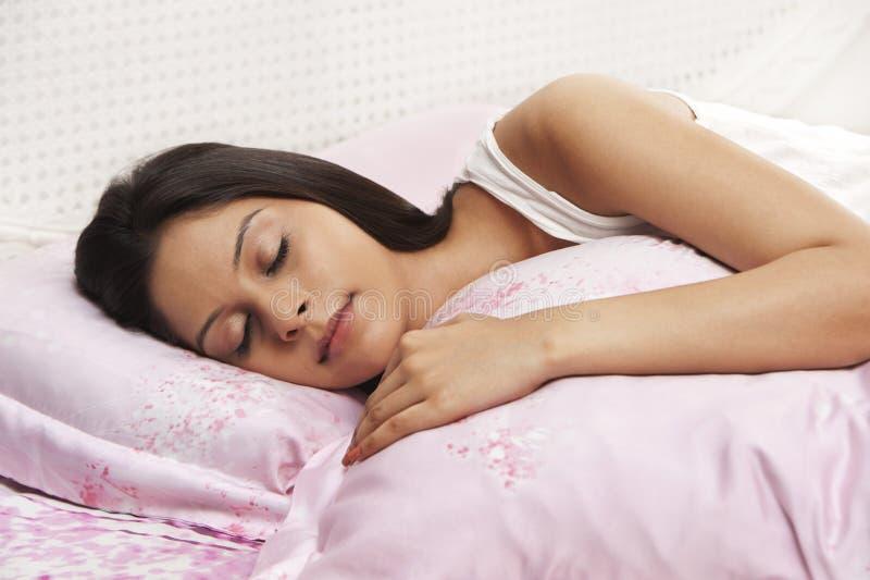 Frau, die auf dem Bett schläft lizenzfreie stockfotos