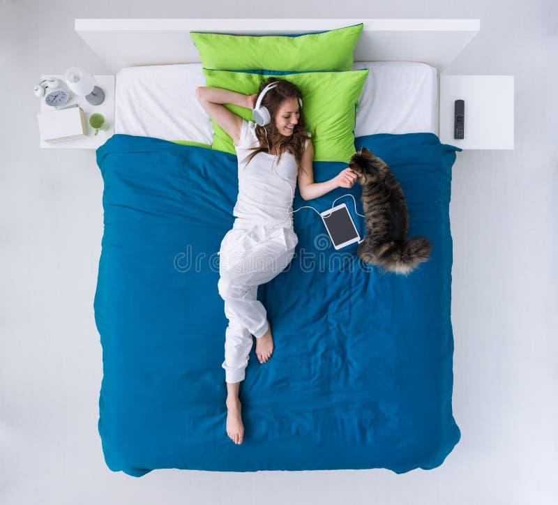 Frau, die auf dem Bett sich entspannt stockfotografie