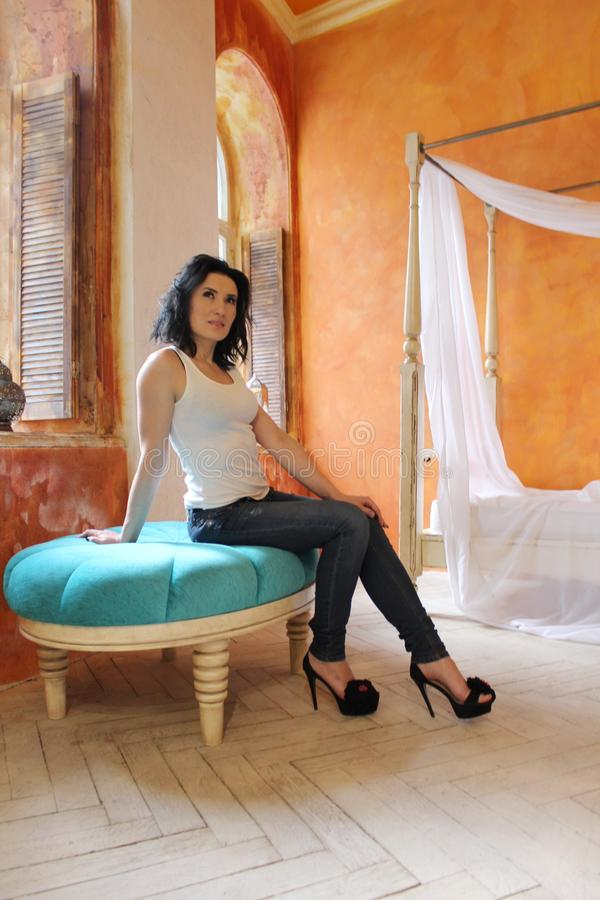 Frau, die auf dem blauen Stuhl sättigt stockfotografie