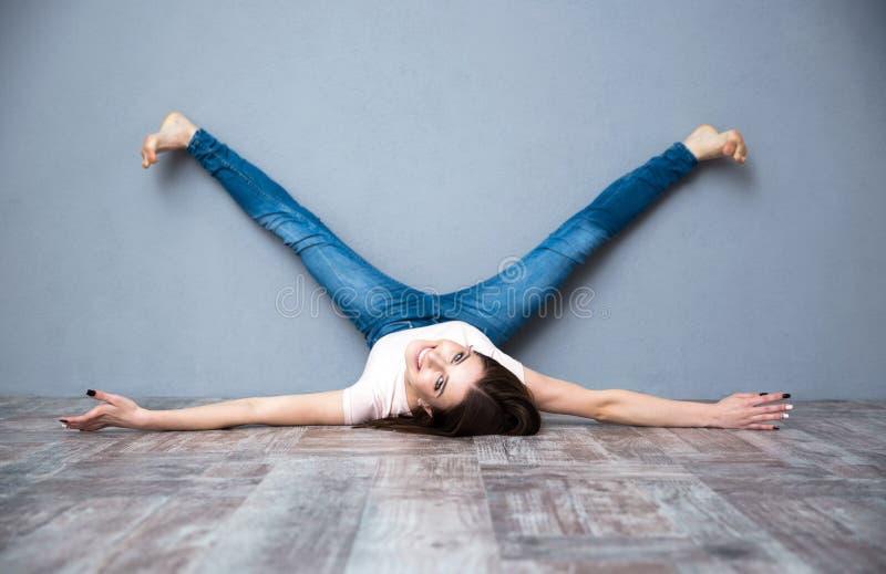 Frau, die auf dem Boden mit den Beinen oben angehoben liegt lizenzfreies stockfoto