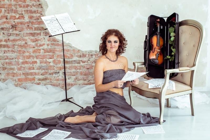 Frau, die auf dem Boden nahe dem Stuhl mit Violine sitzt lizenzfreie stockbilder