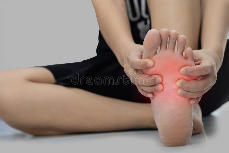 Frau, die auf dem Boden sitzt, den ihre Hand an den Fußschmerz fing stockfotos