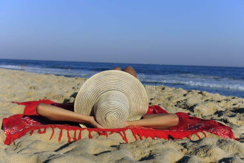 Frau, die auf dem entspannenden Strand liegt lizenzfreie stockfotos