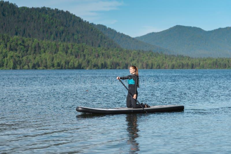 Frau, die auf dem Gebirgssee paddleboarding ist lizenzfreie stockbilder