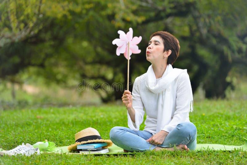Frau, die auf dem grünen Gras genießt die Natur sitzt lizenzfreie stockbilder