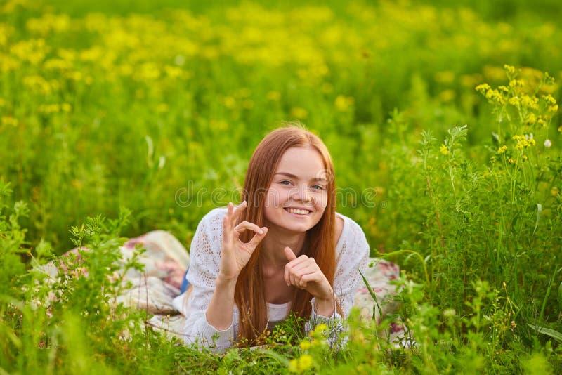 Frau, die auf dem grünen Gras stiiting ist lizenzfreie stockfotografie