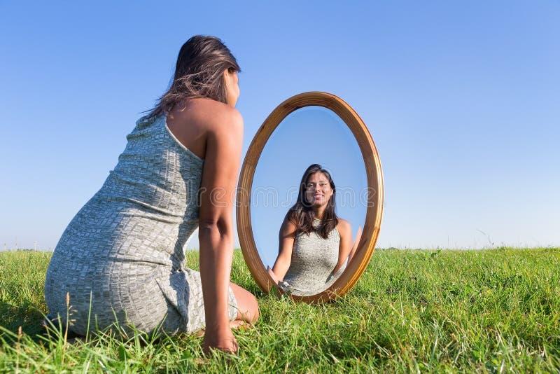 Frau, die auf dem Gras betrachtet Spiegelbild knit stockbilder