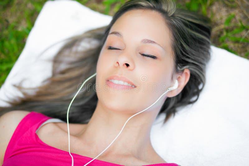 Frau, die auf dem Gras draußen hört Musik liegt stockfotos