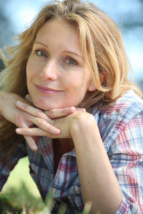 Frau, die auf dem Gras liegt lizenzfreie stockfotos