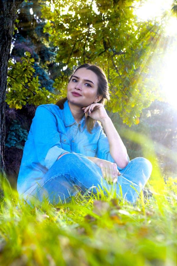 Frau, die auf dem Gras sitzt stockfotos