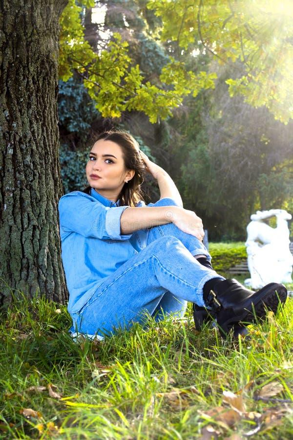 Frau, die auf dem Gras sitzt lizenzfreies stockfoto