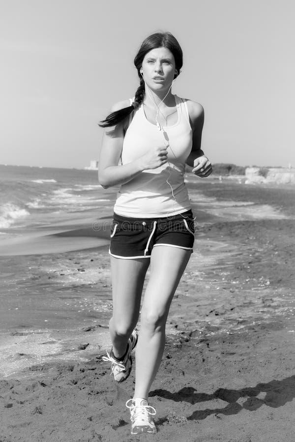 Frau, die auf dem hörenden mittleren Schuss der Musik des Strandes Schwarzweiss rüttelt stockfotos