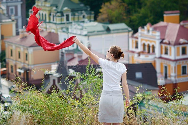 Frau, die auf dem Hügel steht und einen roten Schal wellenartig bewegt stockfotos