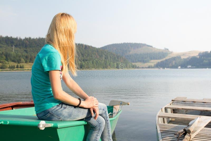 Frau, die auf dem kleinen Boot betrachtet See sitzt lizenzfreies stockfoto