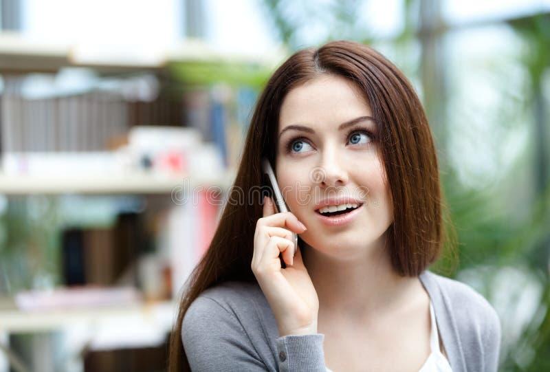 Frau, die auf dem Mobiltelefon spricht stockfotografie