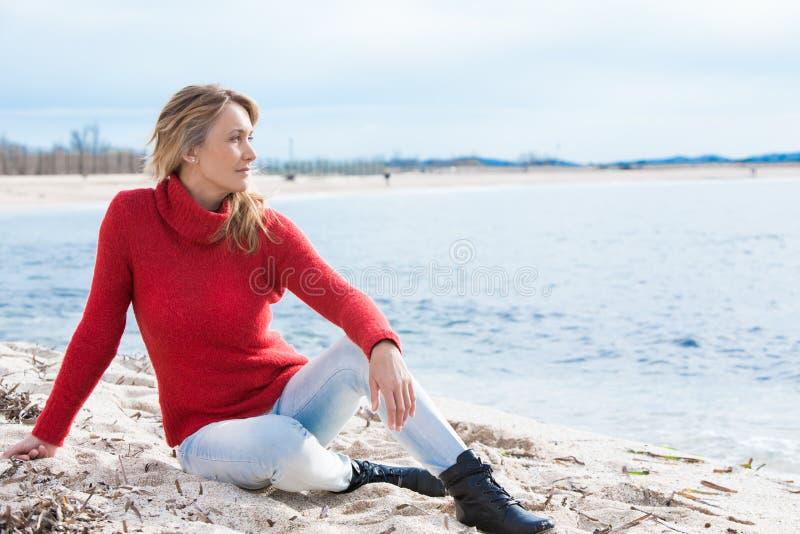 Frau, die auf dem Strand im Winter sitzt lizenzfreie stockbilder