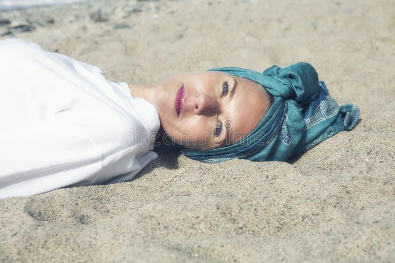Frau, die auf dem Strand liegt und an der Kamera lächelt lizenzfreies stockbild