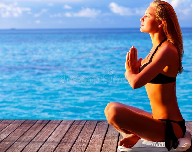 Frau, die auf dem Strand meditiert lizenzfreie stockfotografie