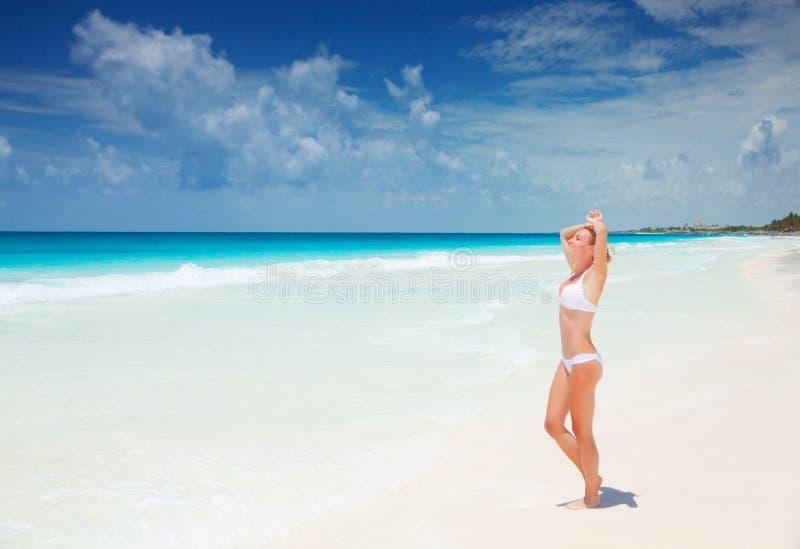 Frau, die auf dem Strand sich bräunt lizenzfreies stockbild