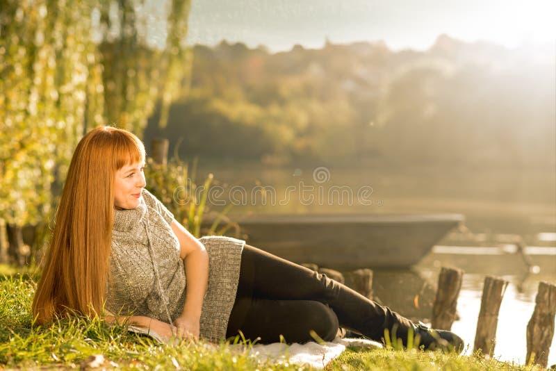 Frau, die auf dem Ufer von See sich entspannt stockbilder