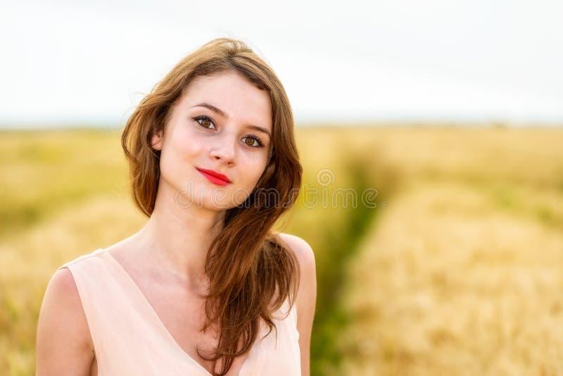 Frau, die auf dem Weizengebiet aufwirft lizenzfreie stockfotografie