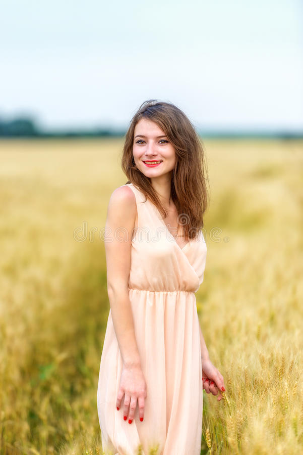 Frau, die auf dem Weizengebiet aufwirft lizenzfreie stockbilder