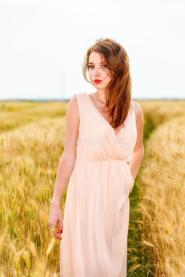 Frau, die auf dem Weizengebiet aufwirft stockfoto
