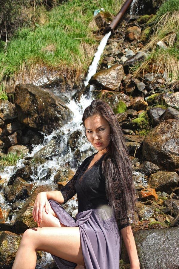 Frau, die auf den Felsen durch den Fluss aufwirft stockbilder