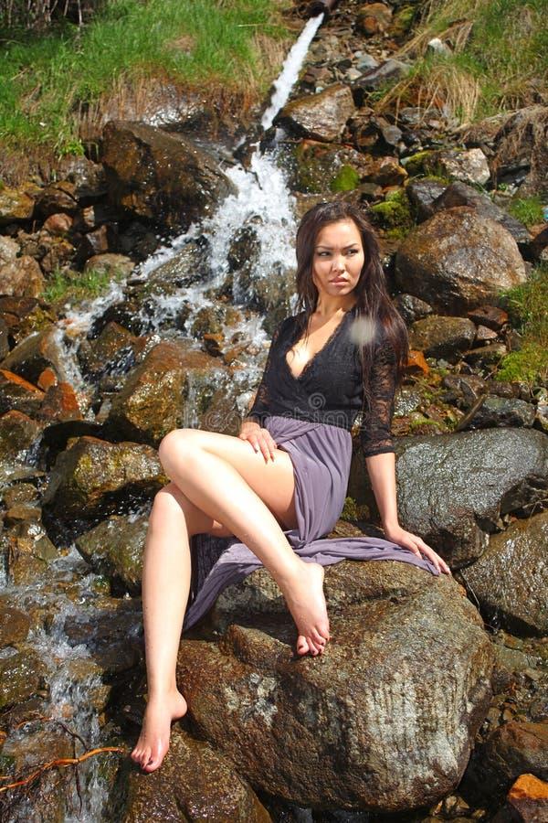 Frau, die auf den Felsen durch den Fluss aufwirft lizenzfreie stockfotografie