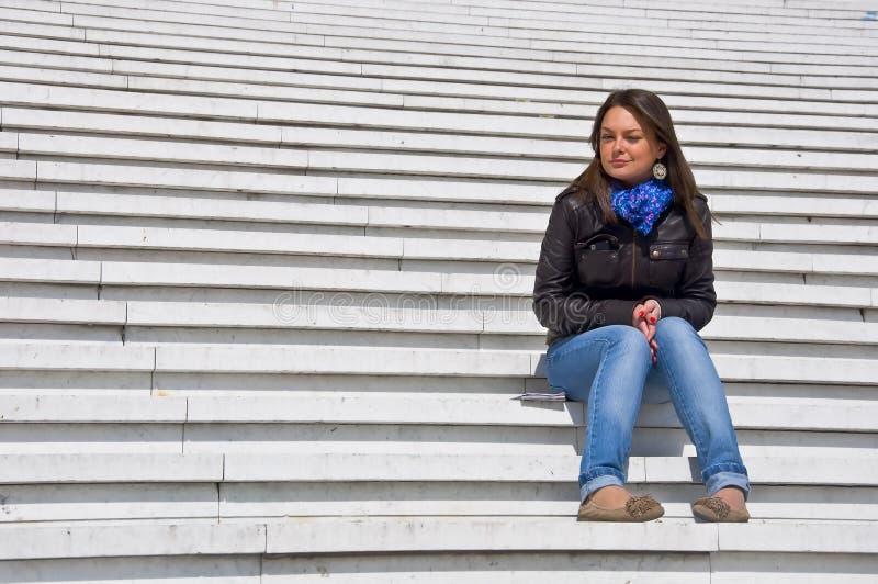 Frau, die auf den Marmorjobsteps sitzt stockfotografie