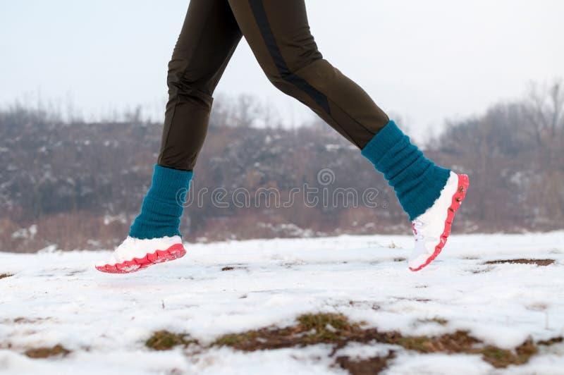 Frau, die auf den Schnee läuft stockfoto