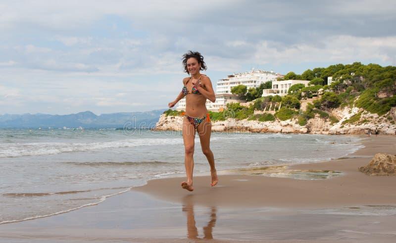 Frau, die auf den Strand läuft lizenzfreie stockbilder