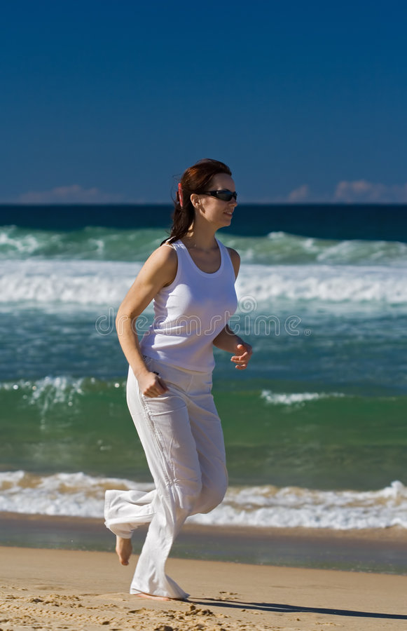 Frau, die auf den Strand läuft stockbild