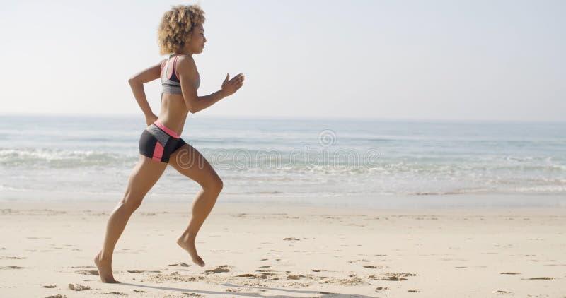 Frau, die auf den Strand läuft lizenzfreies stockfoto