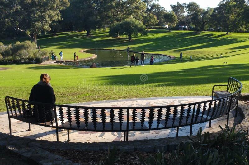 Frau, die auf der Bank am Park sitzt lizenzfreie stockfotos