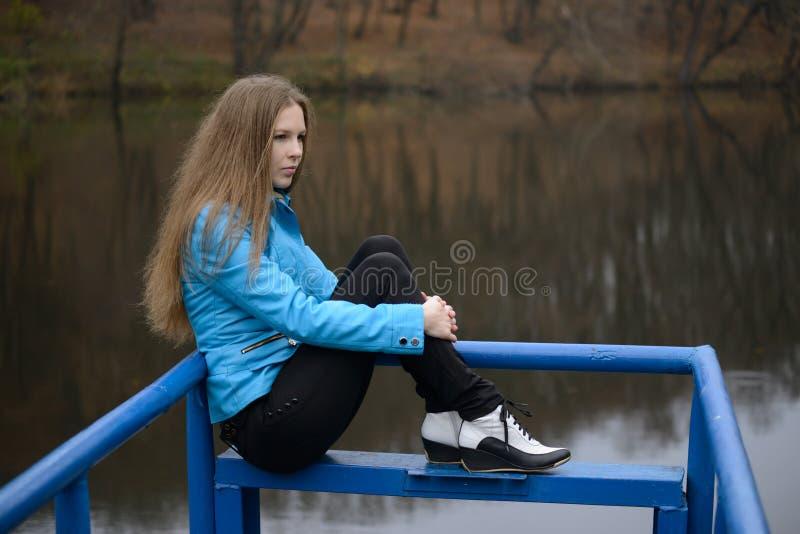 Frau, die auf der Brücke sitzt stockfotografie
