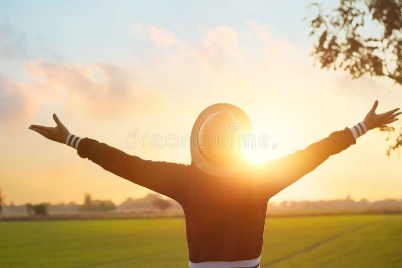 Frau, die auf der grünen Feldlandschaft, angenehm mit Auffrischungsluft auf Freizeitsonnenuntergang sich entspannt lizenzfreie stockbilder