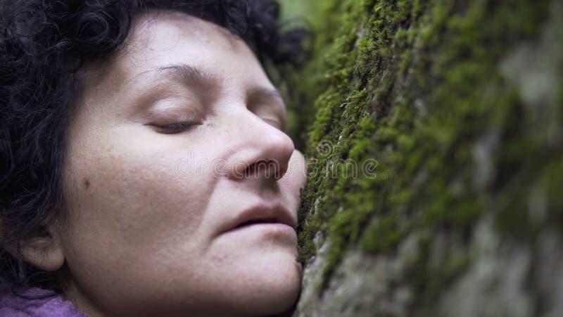 Frau, die auf der Naturhand berührt das Steinmoos im Wald stillsteht stockbild