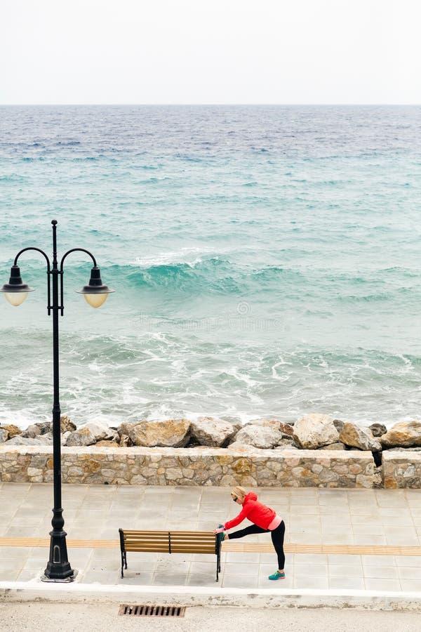 Frau, die auf der Stadtstraße, Meer betrachtend trainiert und läuft lizenzfreies stockfoto