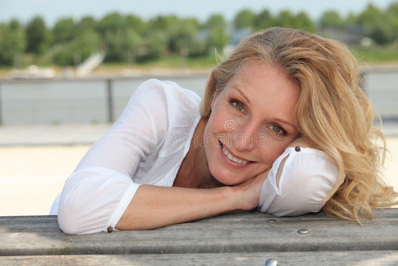 Frau, die auf der Ufergegend sitzt stockfoto